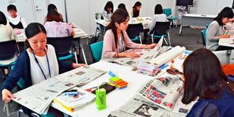 真剣な表情で紙面を読む新入社員=那覇市おもろまち・オリックス・ビジネスセンター沖縄