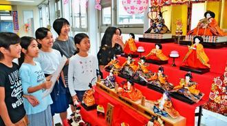 自分たちで飾ったひな壇を満足そうに見つめる金城児童館の子どもたち=20日、那覇市・ゆいレール小禄駅