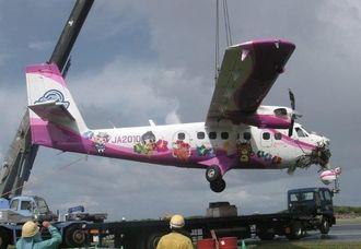 大型クレーン車でつり上げられる第一航空の双発プロペラ機DHC6=31日午後2時すぎ、粟国空港(粟国空港管理事務所提供)