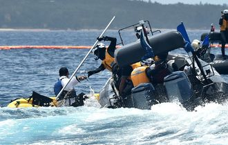 抗議のカヌーを確保する海上保安庁のゴムボート=5日午前11時10分、名護市辺野古沖