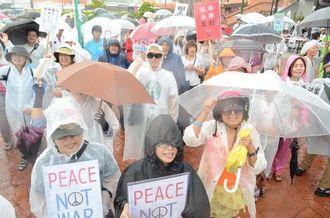 雨の中、集会に参加して平和を訴えた参加者たち=23日、北谷町美浜・カーニバルパーク・ミハマ