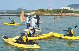 フロートを引き出そうとする作業船を取り囲み抗議するカヌーの市民=12日午前8時41分、名護市辺野古崎付近