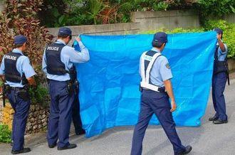 ひき逃げ事件の現場を調べる警察官ら=1日午前8時半ごろ、浦添市宮城