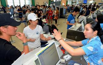 台風8号による欠航で搭乗便の変更手続きをする人たち=10日午後4時ごろ、那覇空港(古謝克公撮影)
