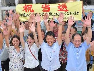 初当選が決まり、支持者と万歳三唱する吉居俊平さん(中央)=9日午後11時27分、名護市大東の選挙事務所(下地広也撮影)