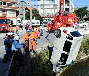 「龍潭」に落ちた軽自動車をクレーンを使って引き上げる消防隊員=9日午前10時23分、那覇市首里