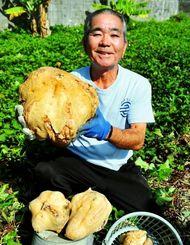 収穫した約7キロの巨大サツマイモを手に笑顔の野里光正さん