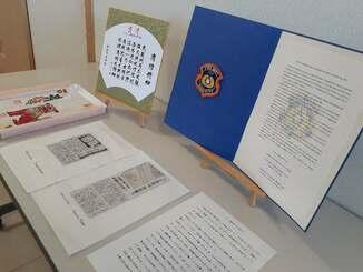 パリ消防局宛てに送るお礼状と紋章ワッペン、地元2紙の掲載紙面=11日、那覇市消防局