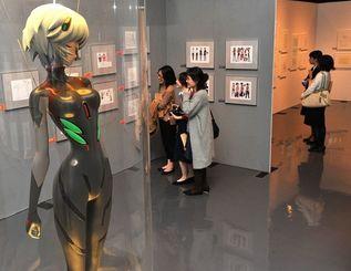 展示された原画や絵コンテに見入る来場者=25日、県立博物館・美術館