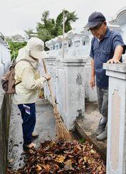 台風8号の影響で汚れた墓の前を掃いて掃除する和宇慶朝一さん、ヨシ子さん夫妻=25日午前、沖縄市古謝(落合綾子撮影)