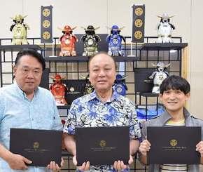 オリガミ・サムライのパッケージを手にするミヤギパッケージの(左から)森武司プロデューサー、宮城通治社長、崎原光明デザイナー=豊見城市の同社