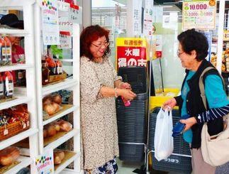 「100円商店街」用に準備したタマネギを販売するハワイアンキルト店「サムシング・グッド」の佐敷美枝子代表(左)=24日、宜野湾市普天間