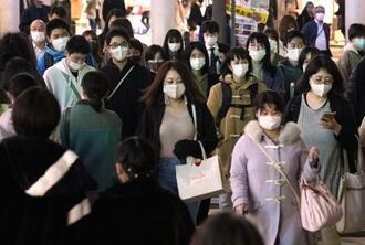 マスク姿で池袋駅付近を行き交う人たち=26日夕、東京都豊島区