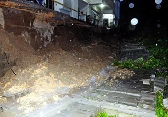 大雨でブロック塀が崩落したアパート=19日午後7時25分ごろ、与那原町板良敷