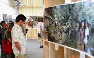 沖縄の歴史の場面を再現した「大琉球写真絵巻」の作品に見入る来場者=4日、東京・なかのZERO西館美術ギャラリー