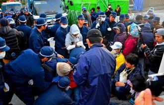米軍キャンプ・シュワブのゲート前に座り込む市民らを排除する機動隊員=12月18日、名護市辺野古