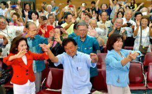 支持者とカチャーシーを踊り、喜ぶ伊波洋一さん(中央)=10日午後8時33分、那覇市古島・教育福祉会館