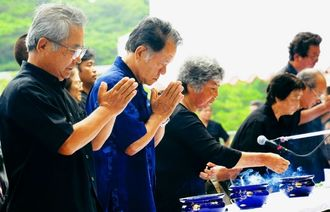 町戦没者慰霊祭でみ霊に手を合わせる遺族ら=町上江洲の戦没者慰霊塔