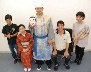 完成した紙の舞台衣装(中央)を囲み笑顔を見せる県立芸術大学の美術工芸学部デザイン専攻、音楽学部琉球芸能専攻琉球舞踊組踊コースの教員と学生=6日、同大・崎山キャンパス