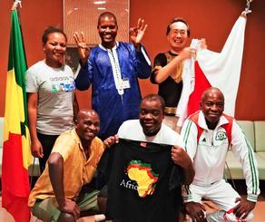 セネガル出身で同国に声援を送るディアロ・ママドウ・ウーリーさん(後列中央)=24日、浦添市