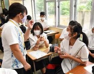 2学期が始まり、担任や同級生と談笑する3年生=11日午前、浦添市・浦西中学校