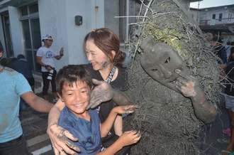 パーントゥに厄払いの泥を塗られる子ども=8日夕、宮古島市平良島尻