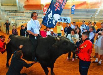 貸し切り闘牛を体験するサンセール伊波の社員ら。記念撮影で「あんやん」に乗る伊波武郎さん=4月20日、うるま市石川多目的ドーム