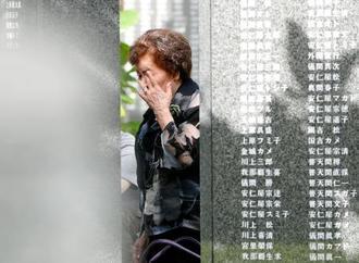 沖縄戦犠牲者の名前が刻まれた「平和の礎」を訪れ、目頭を押さえる女性=23日午前、沖縄県糸満市の平和祈念公園
