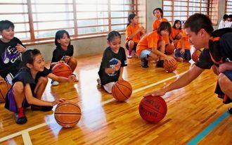 小菅直人選手(右端)から、ドリブルの手ほどきを受ける小学生ら=6日、那覇市・真嘉比小体育館