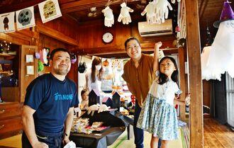 企画展への来場を呼び掛ける「TANONE(タノーン)Shop + Studio」運営の大城盛裕さん(左端)ら=8日、宜野湾市大山の同店