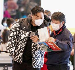 国際線到着ロビーで、マスクを着用して中国人観光客に対応するレンタカー業者=27日午後、那覇空港(下地広也撮影)