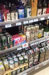 ベトナムのスーパーの酒類コーナーに並ぶオリオンビールの2銘柄(中央棚)=7日、ホーチミン市・イオンモールタンフーセラドン店
