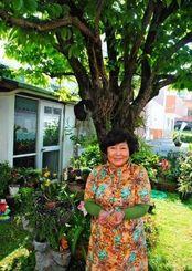 「柿の白や黄色の花がかわいらしい」と話す波平弘子さん=読谷村高志保