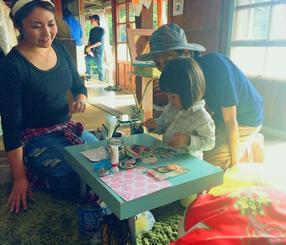 古民家で、ショップの店員(左)に習いながら小物づくりに挑戦する女の子=うるま市与那城伊計