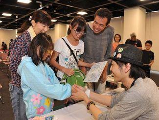 大城さとしさん(右端)からサインをもらい、笑顔をみせる家族連れ=3日、那覇市久茂地・タイムスホール