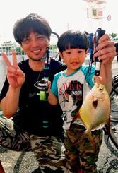 海中道路でマルコバンアジを釣った玉城卓郎さん(左)=4日