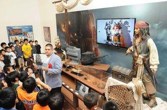 「ディズニー夢と魔法の90年展」の展示物に見入る児童たち=28日午前、那覇市の県立博物館・美術館