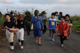 仮面を付けた少年を中心に、集落内を練り歩くサティパロウの参加者=18日午後、宮古島市上野野原