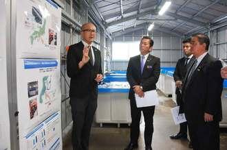 松本哲治市長(左から2人目)らにカキの畜養について説明するジーオー・ファームの佐藤圭一さん(左)=23日、浦添市牧港