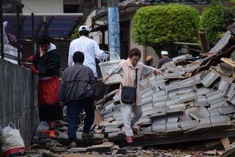 倒壊した屋根瓦の上を歩いて移動する町民ら=16日午後1時25分ごろ、益城町内