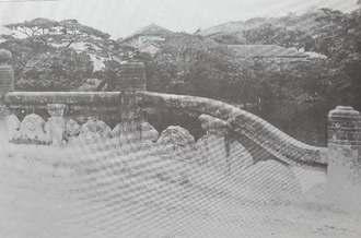 戦前まで架けられていた世持橋。橋の向こうには龍潭や当時の沖縄師範学校校舎が見える(沖縄県立芸術大学附属図書・芸術資料館より提供)