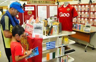 W杯サッカーの日本対戦国を紹介した本も並ぶ「サッカーと読書を楽しもう!」=16日午前、那覇市寄宮・県立図書館