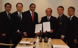 ABSSのラビ・ムティア会長(左から3人目)と契約を交わした忠孝の大城社長(同4人目)=16日、シンガポール市内
