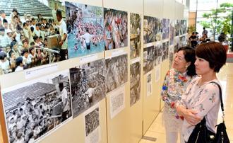 沖縄の世相の移り変わりをモノクロとカラーで振り返る来場者=23日、那覇市のタイムスビル1階エントランス