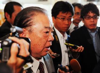 報道陣に囲まれ足早に登庁する安慶田光男副知事=18日午前11時24分、県庁