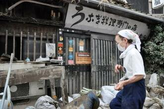 豪雨被害を受けた「上村うなぎ屋」を片付ける上村恵子さん=12日、熊本県人吉市