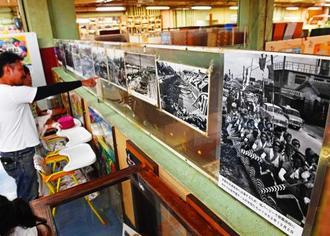 1960年代のガーブ川周辺や市場の盛況を写した写真に見入る来場者=6日正午、那覇市・第一牧志公設市場