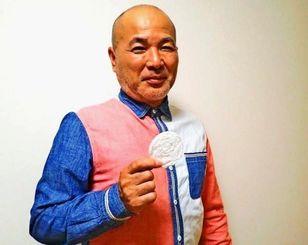 県産シルクを使ったパフの試作品をPRする沖縄UKAMI養蚕の仲宗根豊一代表(同社提供)