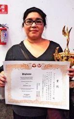 一般グランプリの部で優勝し、トロフィーと賞状を手に笑顔を見せる伊集ジュリアナさん