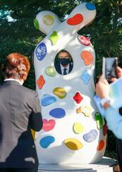 「東京2020 復興のモニュメント」の視察に訪れ、穴から顔を出すIOCのバッハ会長。橋本聖子・大会組織委会長らが記念撮影していた=1日午後、東京都新宿区